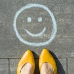 Symbol of happy smiley drawn on the asphalt and woman feet.